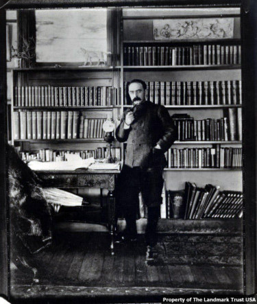 Rudyard Kipling holds and pipe in his hand and stands next to a table in fornt of shelves filled with books