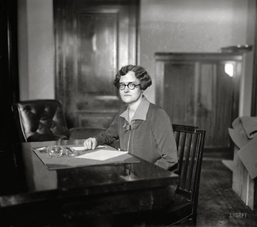 Mary Jean Simpson seated at desk in Senate office.
